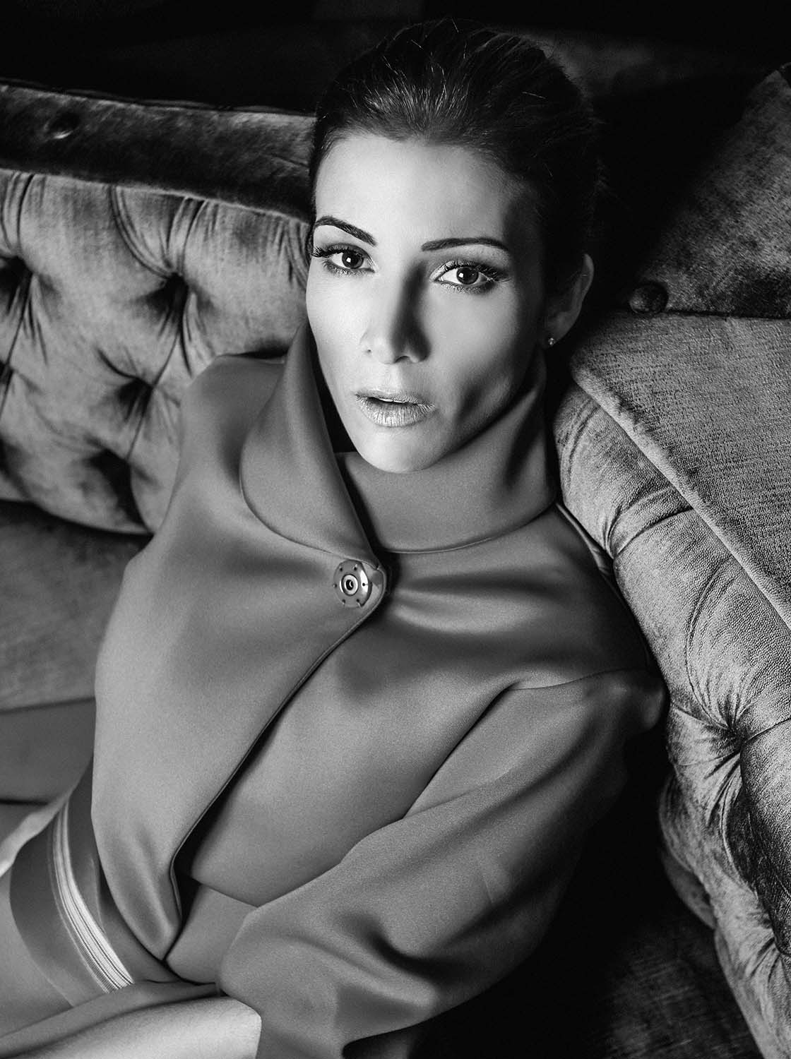 classic black and white photo of virginia troconis sitting on a sofa