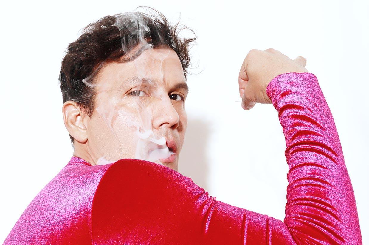 jorge matamoros se fuma un cigarro con body de mujer de terciopelo rojo de manga larga