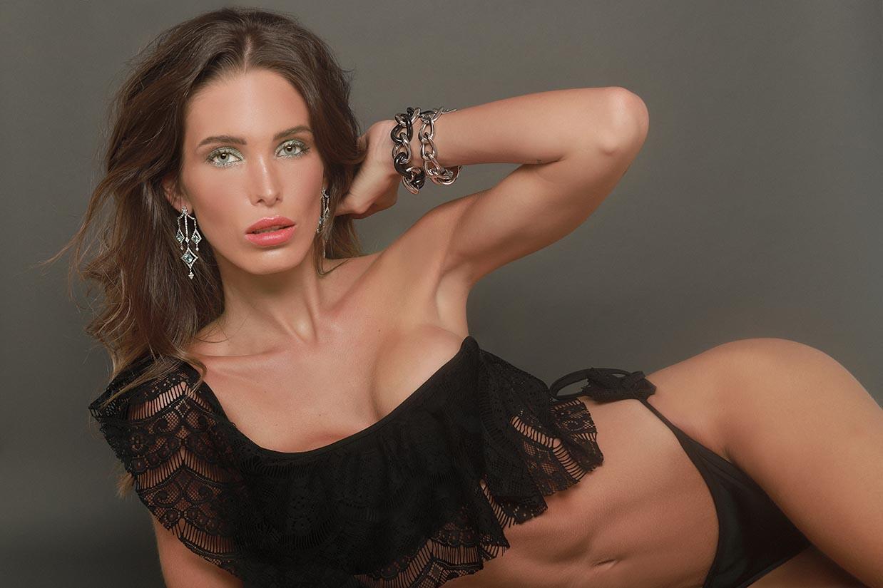 marta lopez alamo posa tumbada en bikini negro con pulseras y pendientes